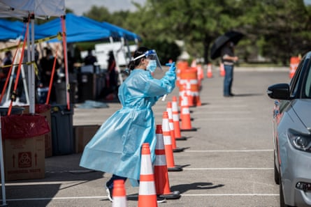 : A nurse beckons to people in a car at a newly opened mega drive-thru site at El Paso Community College Valle Verde campus on July 21, 2020 in El Paso, Texas. As coronavirus deaths surge past 4000 in Texas, overwhelmed hospitals are being forced to plan for extra refrigerated storage to hold deceased patients.
