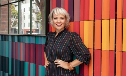 a blonde woman stands in front of a multicoloured stripy wall