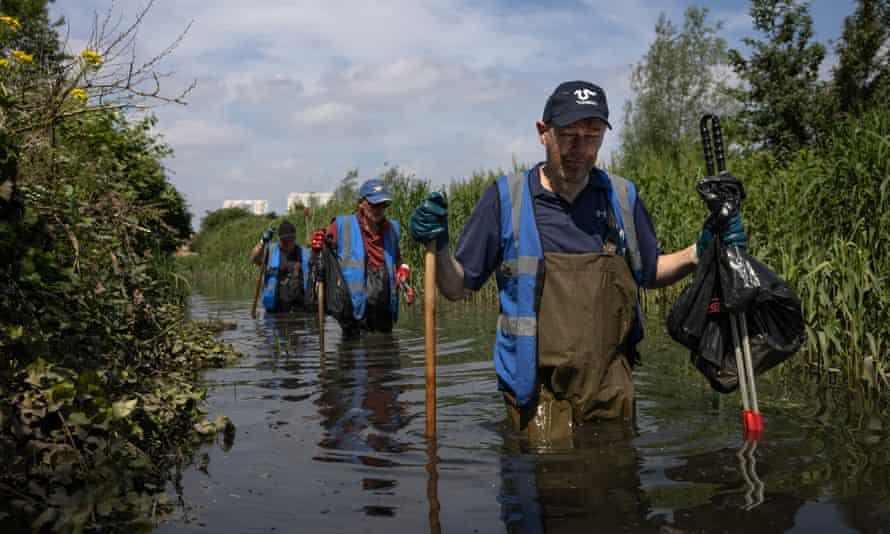 A river cleanup organised by the waterway advocacy group Thames21 in London, removing litter and plants such as Himalayan balsam.