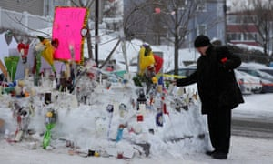 A man puts a candle at the memorial near the site of the shooting in Québec City.