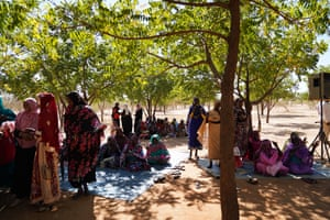 Women under the shade of the trees they planted during the performance of Sasa.