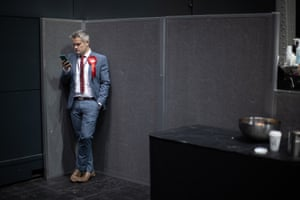 A Labour campaigner on his phone at the count for seats in North West England