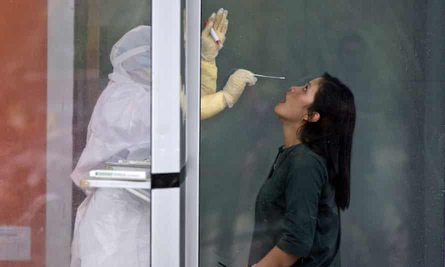 A medical worker prepares to collect nasal swab samples from a woman during a mass test for Covid at North Sumatra University in Medan, Indonesia.
