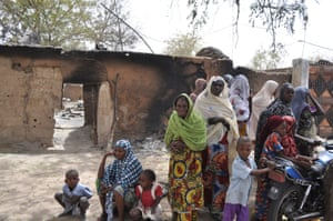 Women and children in Gubio, Nigeria, are seen outside a burnt house following an attack by Boko Haram militants in May 2015