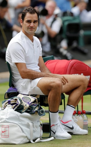 A tearful Roger Federer sits in his chair awaiting the trophy presentation