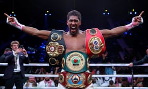 Anthony Joshua shows off the WBA, IBF, WBO and IBO heavyweight titles belts.