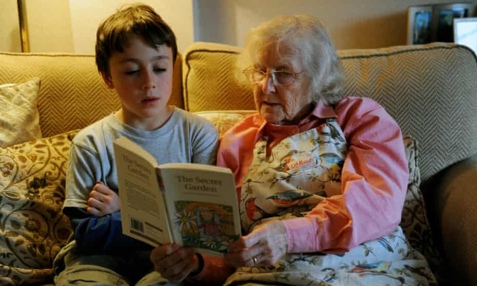 Grandmother listening to grandson read on sofa
