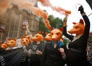 London, England Anti-fox hunting protesters hold smoke flares as they demonstrate outside Parliament