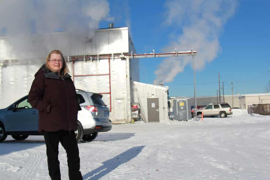 Patrice Lee stands in front of a kiln where wood is dried before it is sold, in an effort to limit air pollution.