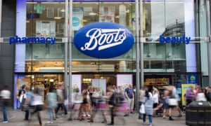 Shoppers walking past a branch of Boots in Oxford Street, London