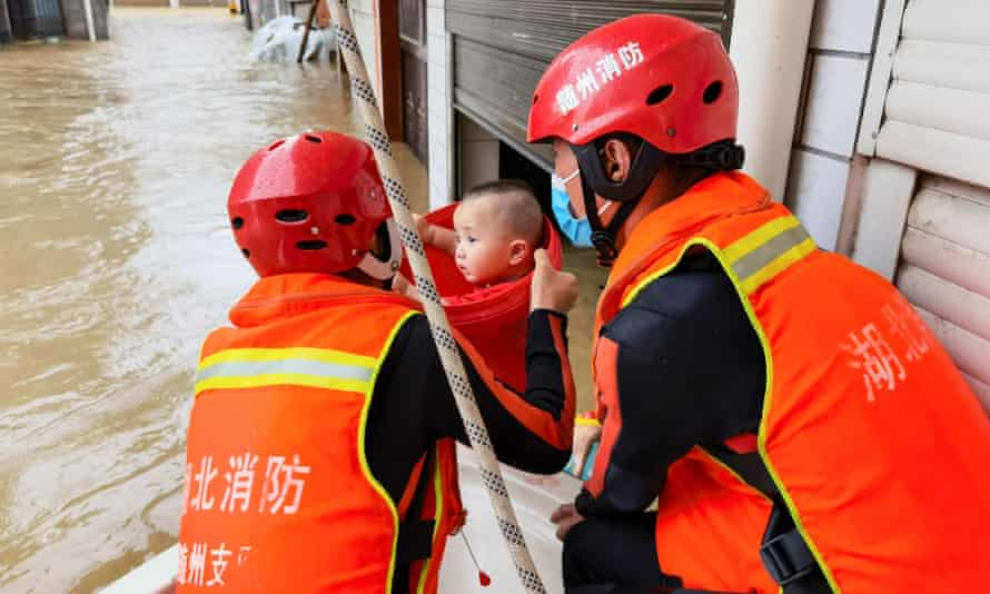 Rescuers evacuating a child from the floodwaters in Suizhou in Hubei