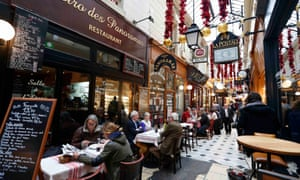 People sit outside bistros for lunch in the Passage des Panoramas, Paris.