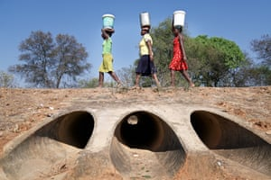 Three women carry 20-litre buckets of water back from the nearest borehole four kilometres from their homes, the area's only remaining source of water. The water way beneath them has run dry