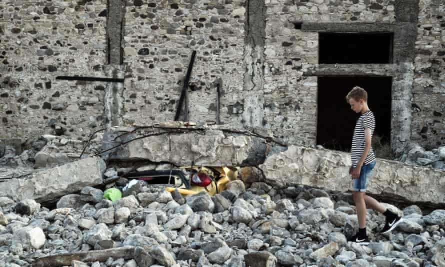 A boy stands next to a car crushed under rubble on Kos