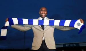 Sol Campbell holds up a Macclesfield scarf