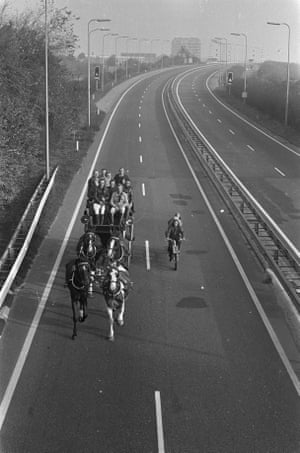 A stagecoach drives on the highway, accompanied by a cyclist