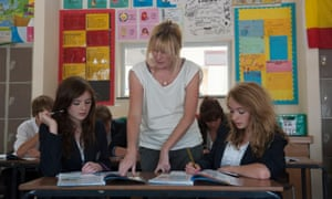 Female teacher in classroom with teenage students