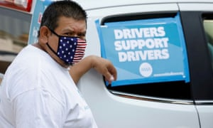 """Rideshare driver Jesus Jacobo Zepeda of Lancaster, California takes part in a rally to demand that ride-hailing companies Uber and Lyft follow California law and grant drivers """"basic employee rights'', in Los Angeles, California, August, 2020."""