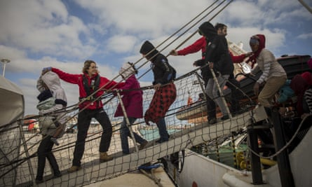 Aid workers help refugees and migrants to disembark a rescue vessel in Sicily, Italy.