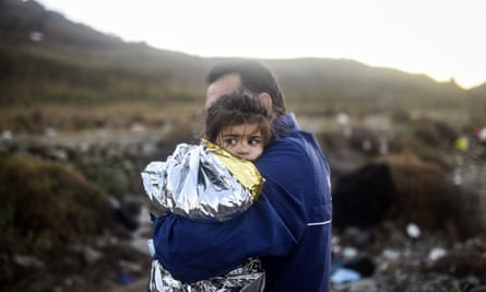 A man holds a young girl after arriving with other refugees at the Greek island of Lesbos