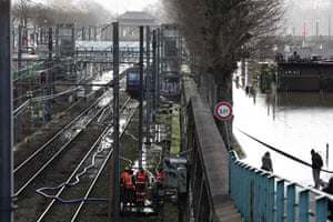 Workers pump water from the Javel railway station