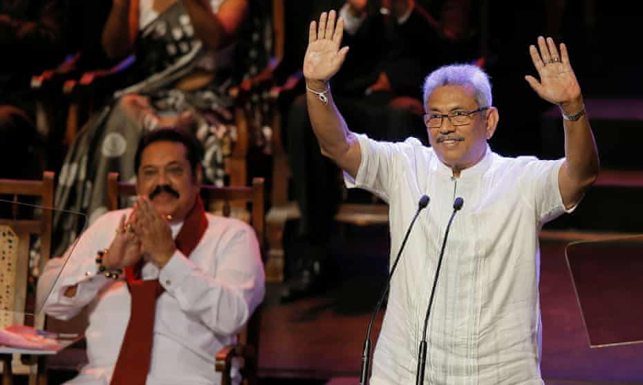 The SLPP's presidential candidate, Gotabaya Rajapaksa, waves to party members while his brother, Mahinda Rajapaksa, applauds