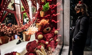 A passerby gazes at Christmas decorations in a window in Milan, Italy