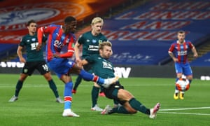 Palace's Wilfried Zaha shoots as Charlie Taylor of Burnley attempts to block.