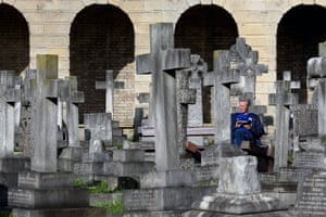 A Chelsea fan sits among the gravestones of West Brompton Cemetery on their way to their game against Newcastle United at Stamford Bridge