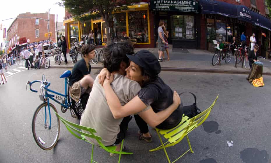 Two people hug on a street in Brooklyn.