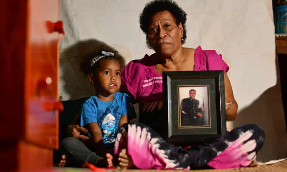 Nainasa Valetabua with her three-year-old grand-daughter Marica Duikoro at her home in Lami, Fiji. She hold a picture of her son, Taitusi Ratucaucau, a British Army veteran whose life is in limbo since his contract was terminated.