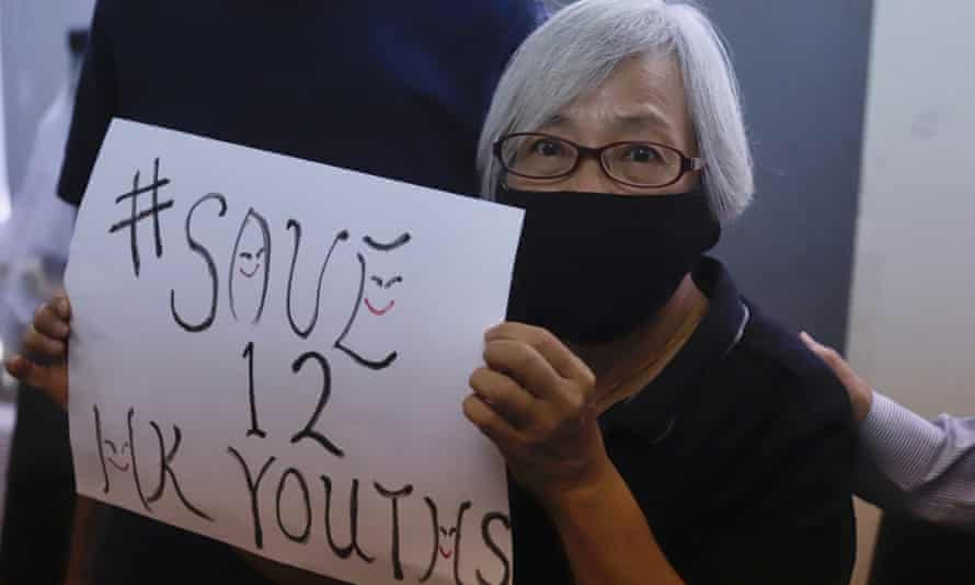 A pro-democracy activist displays a #save12HKyouths poster calling for the release of the youths held since they tried to escape Hong Kong for Taiwan by boat.
