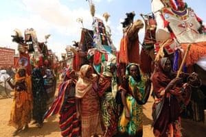 Women guide decorated camels in Umm al-Qura during the visit of Sudanese President Omar al-Bashir to the war-torn region.