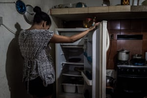 A woman stares into her empty fridge at her house in Petare
