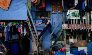 A police officer moves between houses during a police operation against illegal drugs at a slum area in Manila.