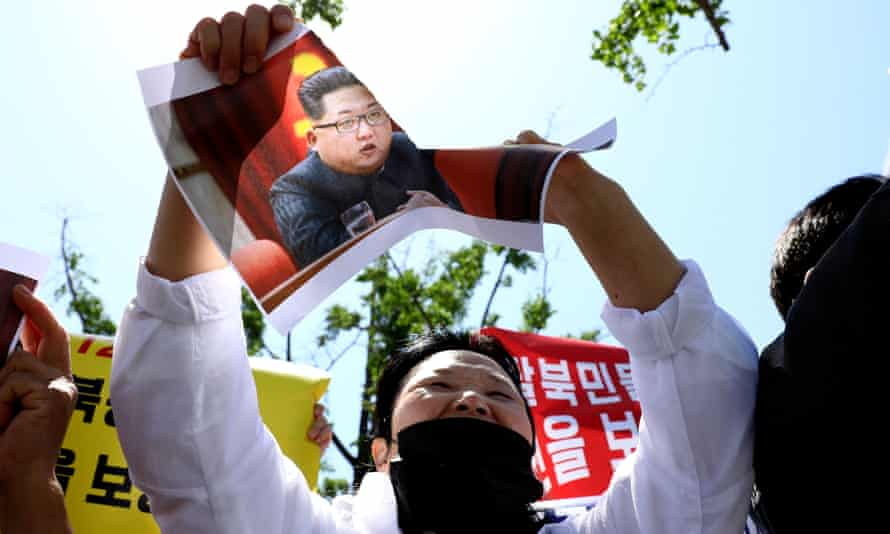 A North Korean refugee tears a portrait of Kim Jong-un during a rally in May in Seoul, South Korea.