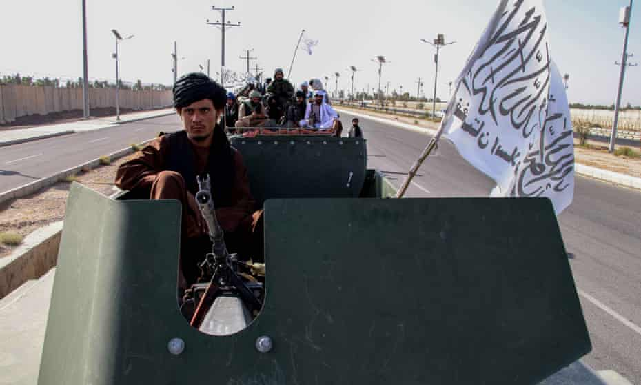 Taliban forces rally to celebrate the withdrawal of US forces in Kandahar, with plundered US military hardware.