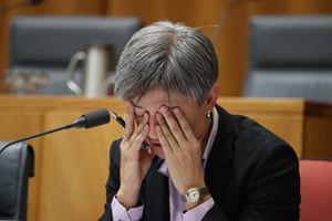 Penny Wong holds her hands over her eyes