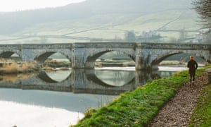 Woman trail running by river, North Yorkshire