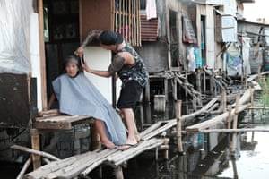 Across the street from the cemetery, there is a row of squatter homes above sewage water. This woman is paralyzed from the waist down, and has not had her haircut in ages.