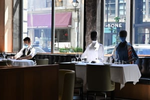A waiter prepares a table next to mannequins at a restaurant in old Montreal, Canada. The mannequins not only ensure social distancing but also wear outfits that can be bought to help charities.