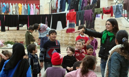 An aid worker conducts an exercise class for children at a center in Tartous for Syrians displaced by the civil war