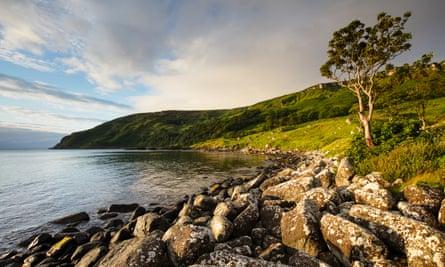 Early morning sun illuminates the coastline of Murlough Bay, near the coastal town of Ballycastle.