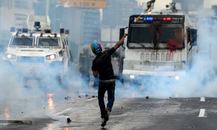 Opposition activists and riot police clash during a protest against the Venezuelan president in May.
