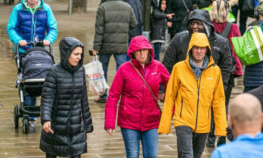 Pedestrians in Wimbledon town centre walk in the rain, 16 May 2021.