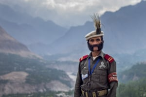 Medium shot of a uniformed soldier, Salahuddin, who is the security detail at Baltit Fort in northern Pakistan, which overlooks the epic Hunza valley – which can be seen in the background of the image.