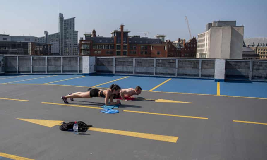 A man and a woman exercise on top of a multistorey car park in Manchester.