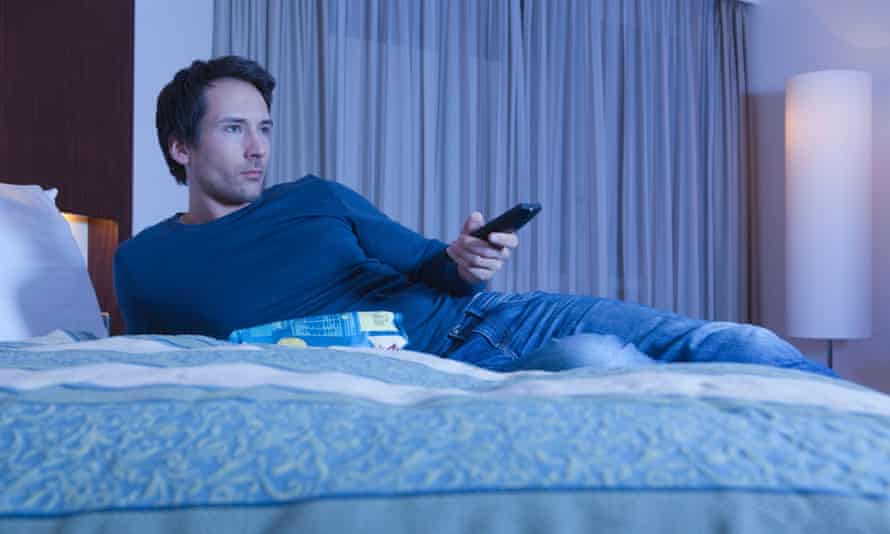 A man on a bed watching TV