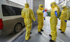 Funeral parlour workers in protective suits in Wuhan, China, disinfect themselves