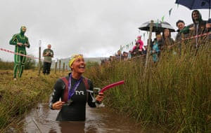 A competitor in a wetsuit celebrates finishing the race